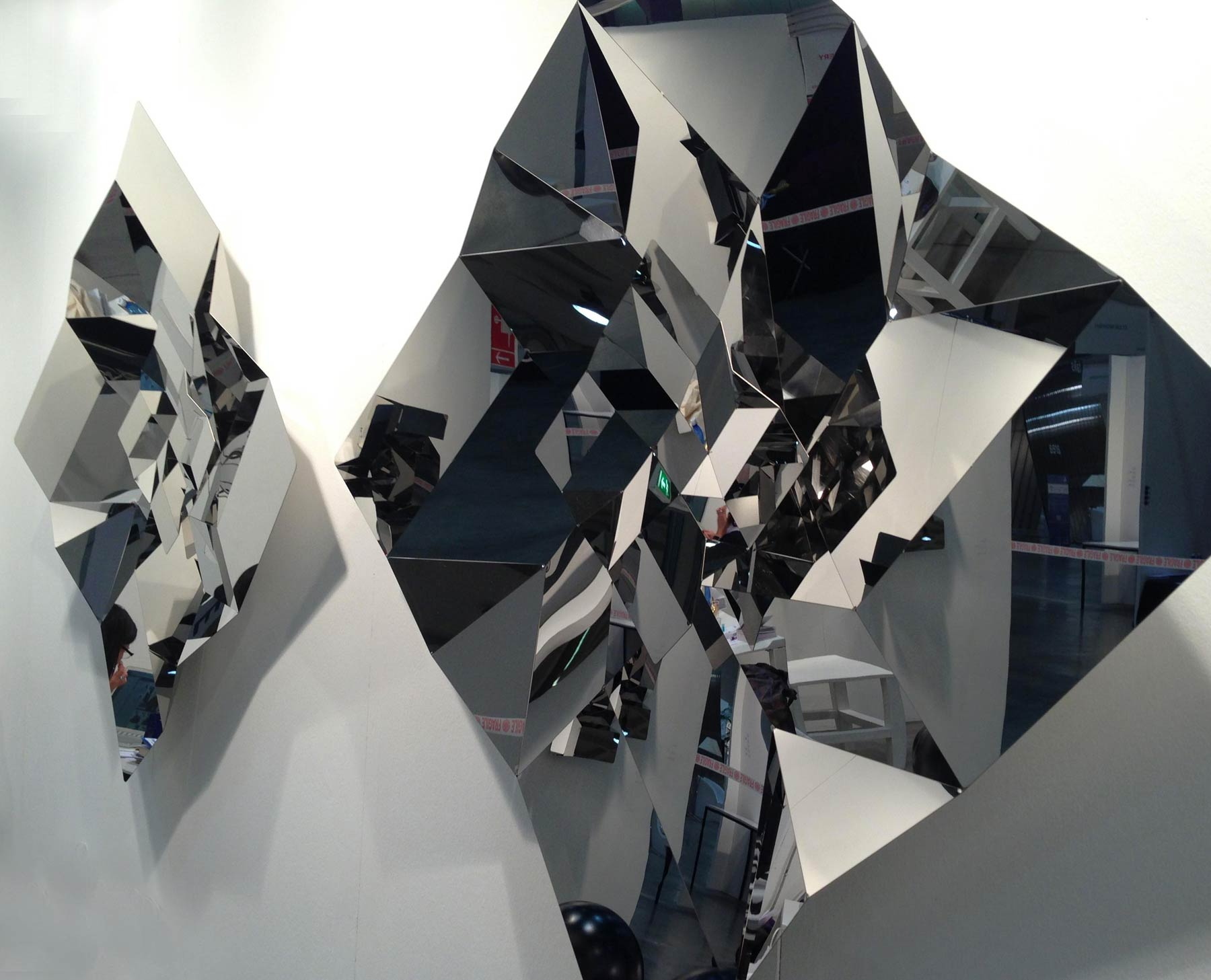 Picture of folded metallic panes placed on a wall.