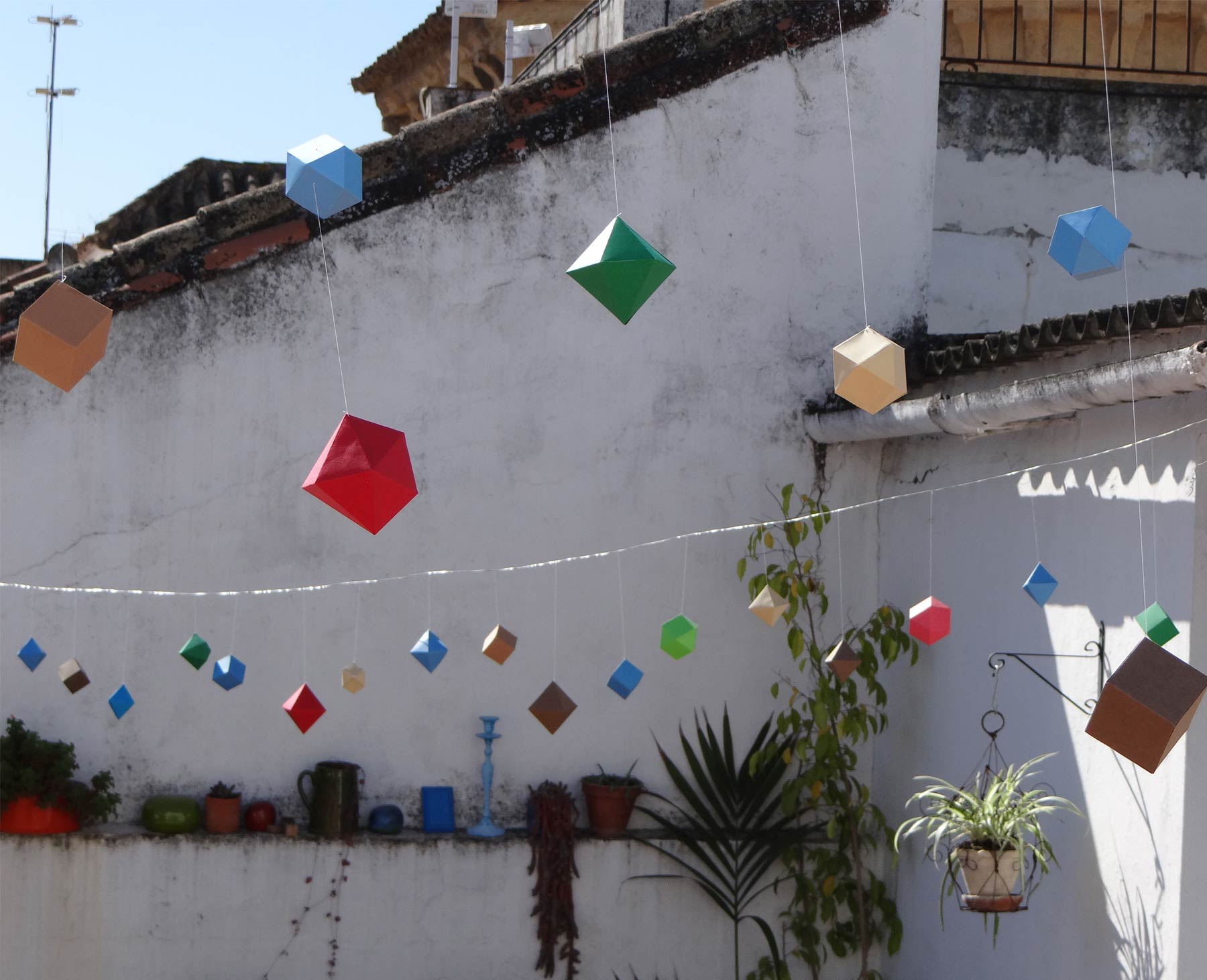 Photo of a terrace decorated with coloured small three-dimensional geometrical paper items
