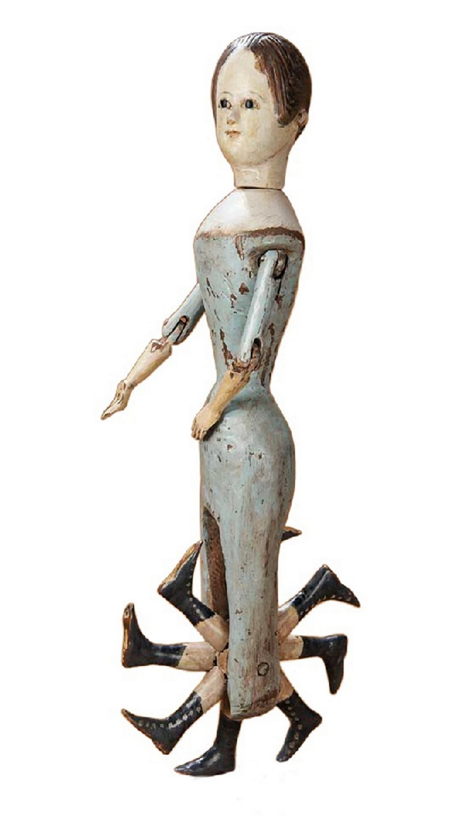 A wooden doll. Her legs have been replaced by a mechanical set of 8 shoes